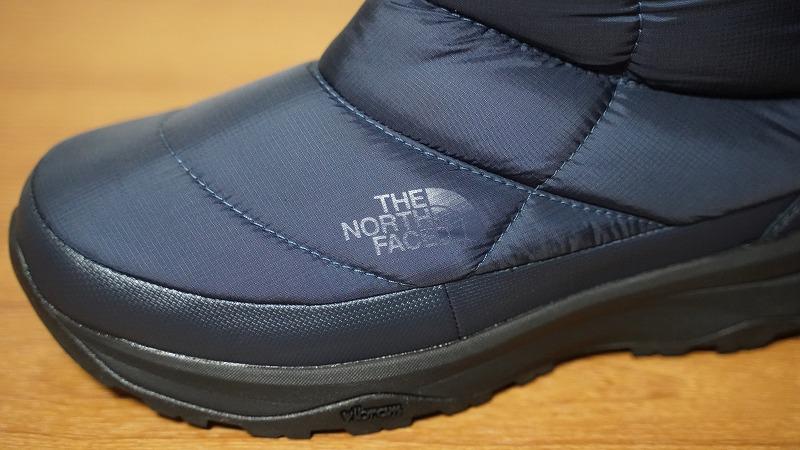 THE NORTH FACE(ザ・ノースフェイス)のスノーブーツ「ヌプシブーティーウォータープルーフVI」-同色のロゴ-光の反射