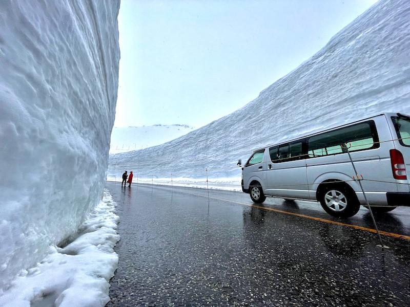 人と車が入った雪の大谷の写真